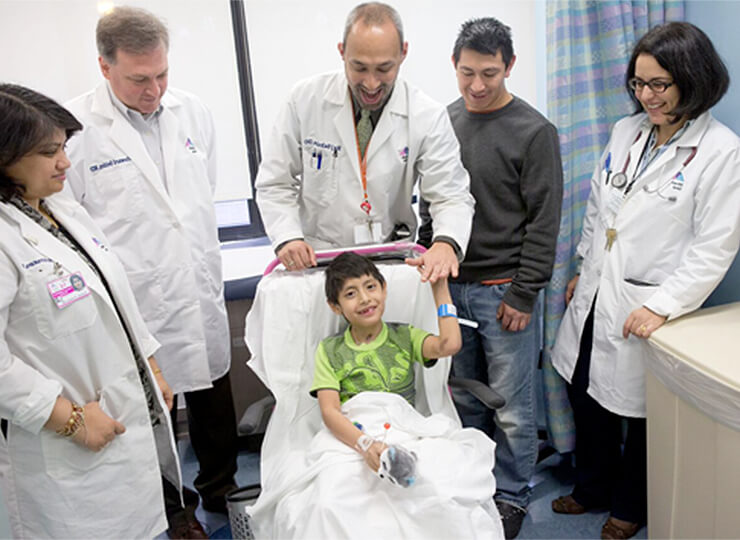 Photo of Little boy surrounded by doctors and father