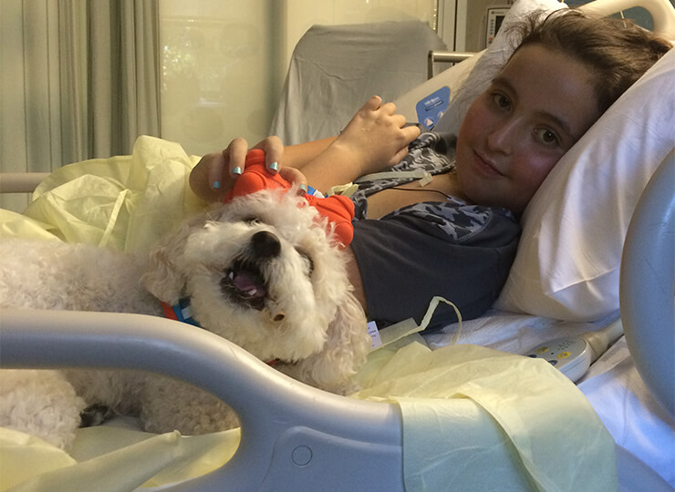 Photo of Girl with white dog in hospital bed