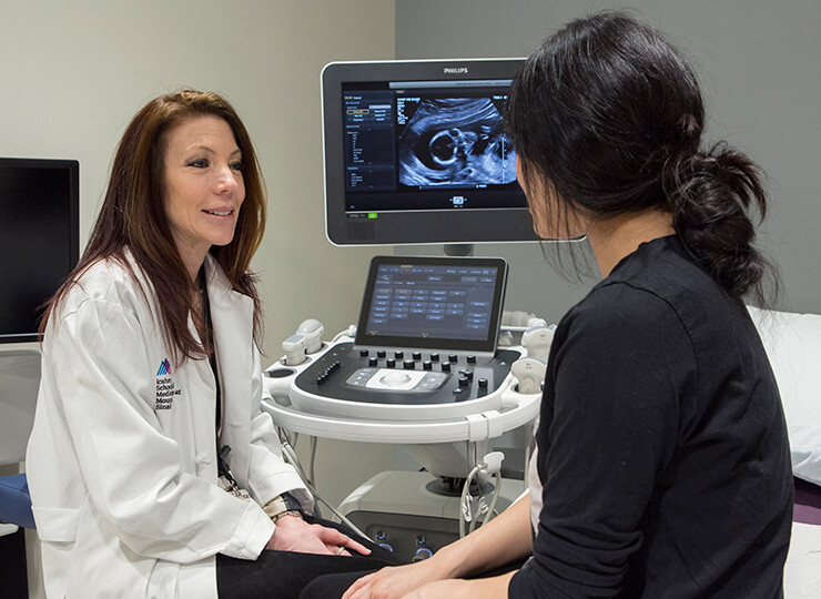 Photo of Doctor talking to pregnant patient following sonogram