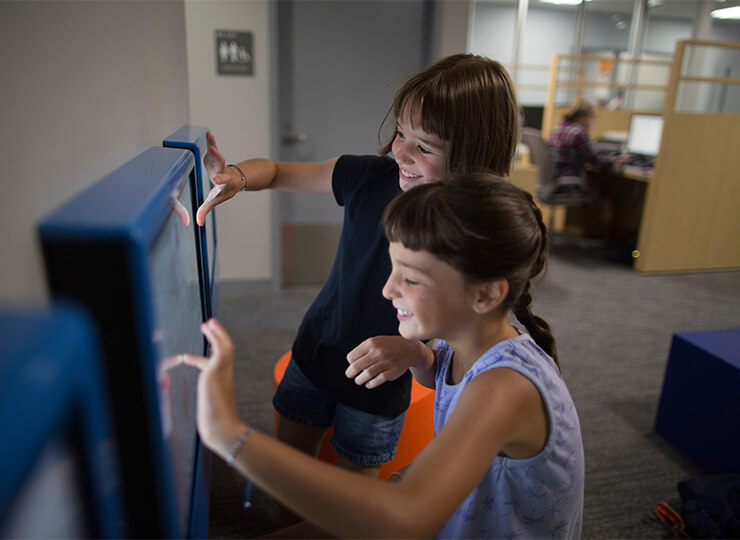Photo of two girls playing on computer in waiting room