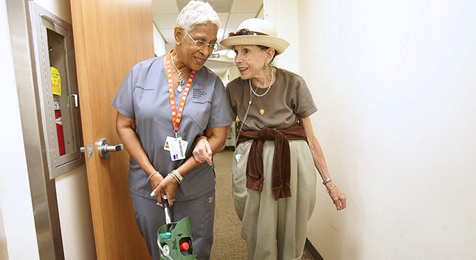 Two women walking down a hallway
