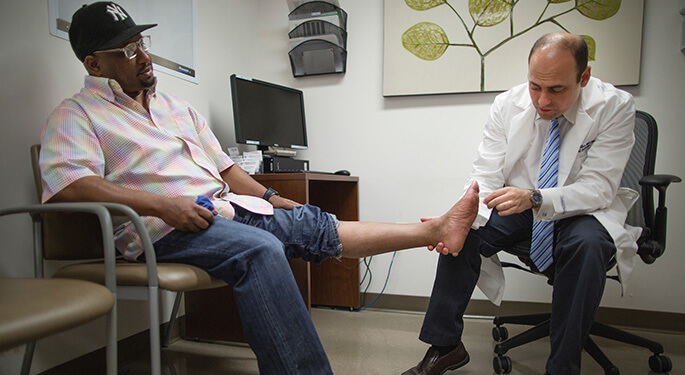 Dr. Ronald Tamler examines foot of seated patient
