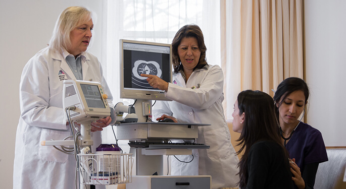 Two doctors explaining a scan to patient while nurse listens to patient