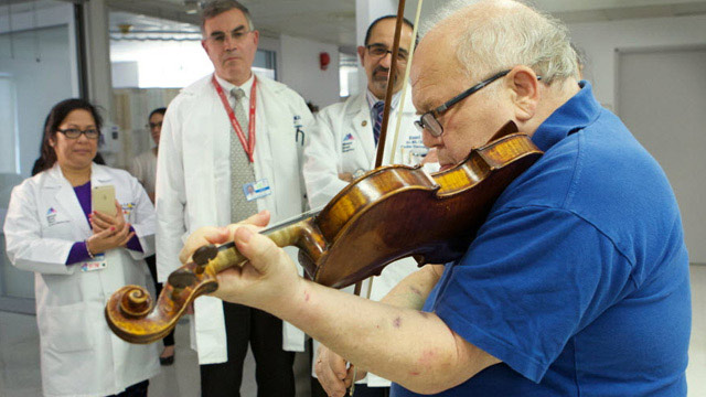 violin being played with doctors in background